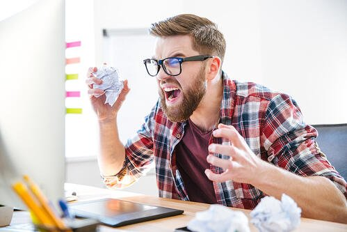 Angry crazy modern designer in glasses with beard yelling and crumpling paper on his workplace-1