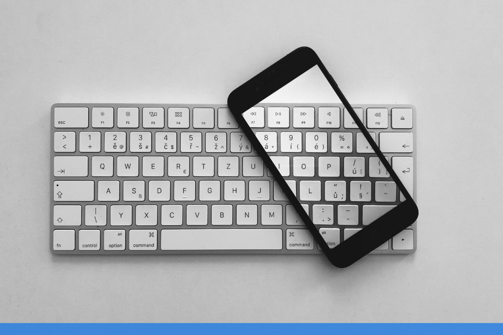 closed up of mobile resting on a white keyboard