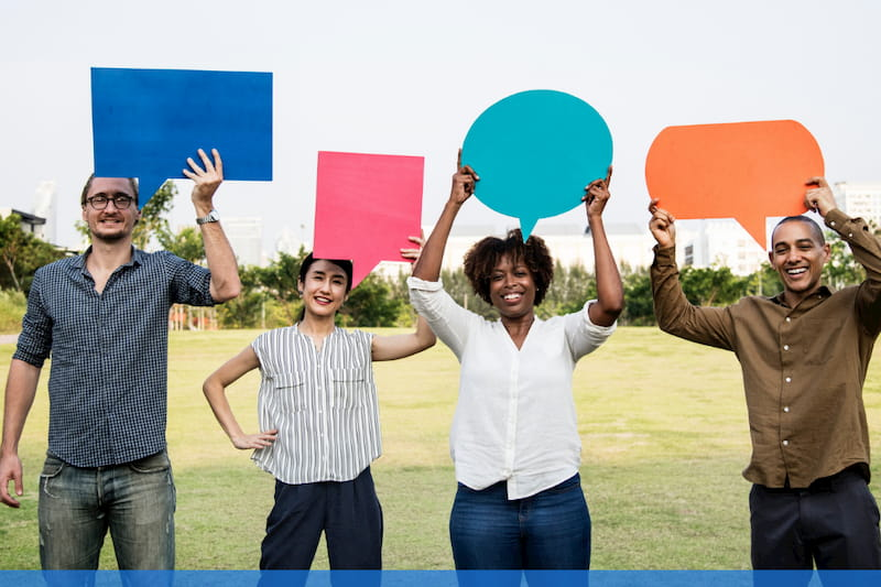 Employees smiling and holding speech bubbles