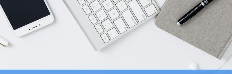 White phone, white keyboard, grey mousepad and black pen