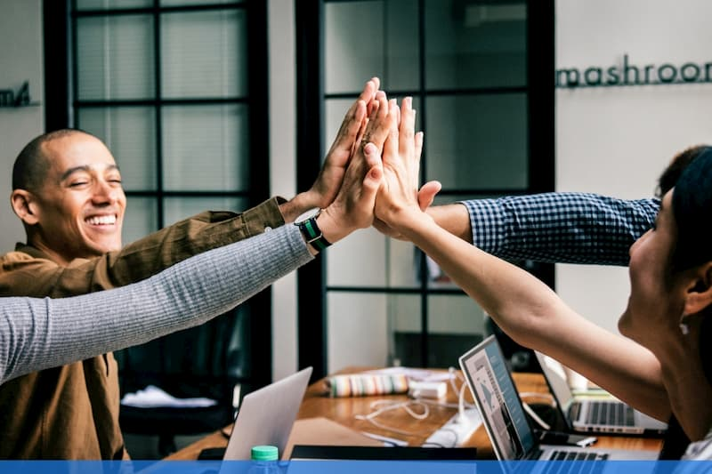 Employees high-fiveing each other at work